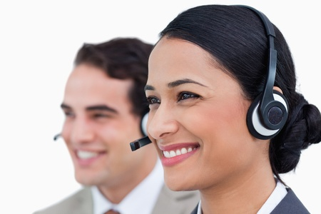 Close up side view of smiling call center agents against a white background photo