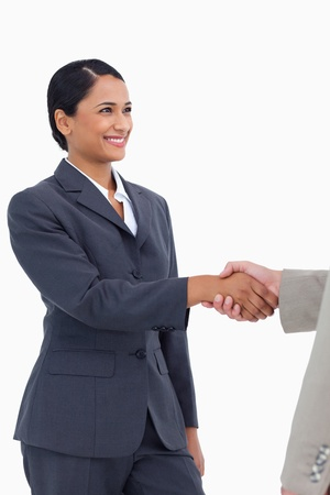 Smiling saleswoman shaking hand against a white background Stock Photo - 13659231