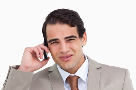 Close up of irritated salesman on his cellphone against a white background photo