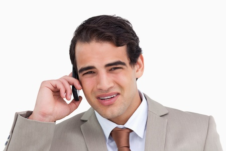 irritating: Close up of annoyed young salesman on his cellphone against a white background Stock Photo
