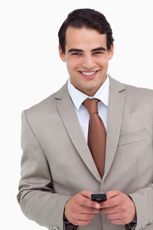 Close up of smiling salesman holding his cellphone against a white background photo