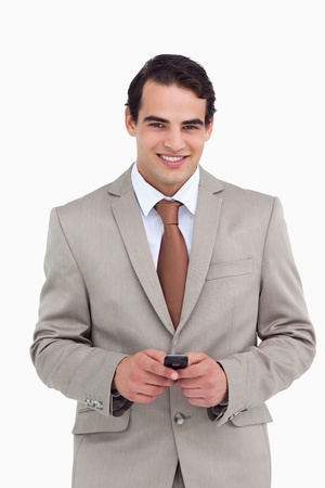 Smiling salesman holding his cellphone against a white background photo