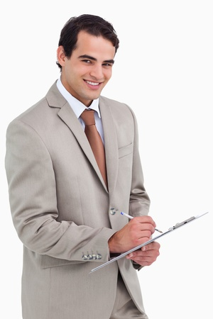 Smiling salesman with notepad and pen against a white background photo