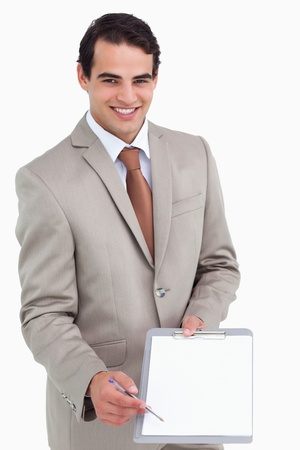Smiling salesman asking for signature against a white background photo