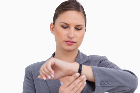 Businesswoman checking her watch against a white background Stock Photo - 13653707