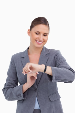 Smiling businesswoman looking at her watch against a white background Stock Photo - 13673568