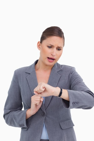 late 20s: Shocked businesswoman checking her watch against a white background