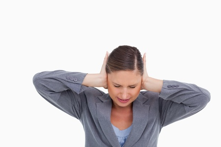 Close up of irritated tradeswoman covering her ears against a white background photo