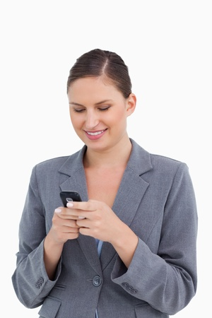 Close up of smiling tradeswoman reading text message against a white background photo