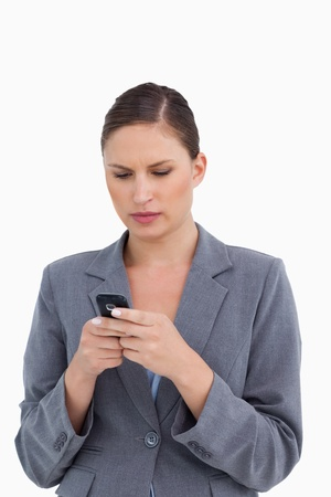 Close up of tradeswoman reading text message against a white background photo