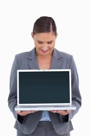 Smiling tradeswoman looking down at her laptop against a white background photo
