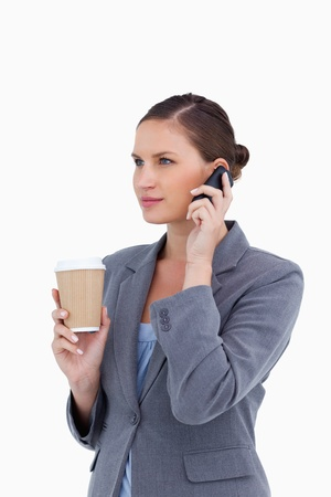Tradeswoman with paper cup on her cellphone against a white background photo