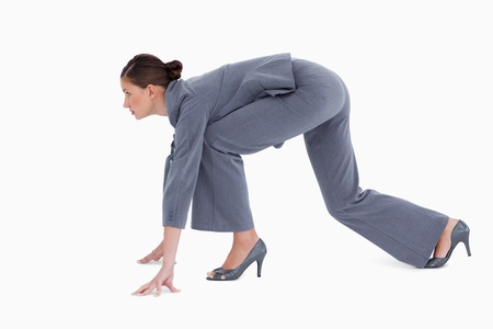 Side view of tradeswoman in sprinting position against a white background photo