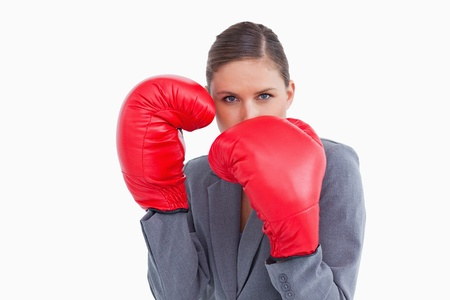 Tradeswoman with boxing gloves in defensive position against a white background photo
