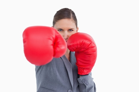 tradeswoman: Tradeswoman with boxing gloves attacking against a white background Stock Photo