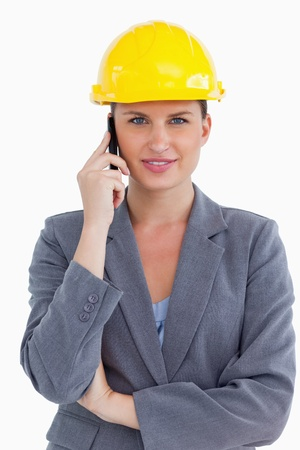 Smiling female architect on her cellphone against a white background photo