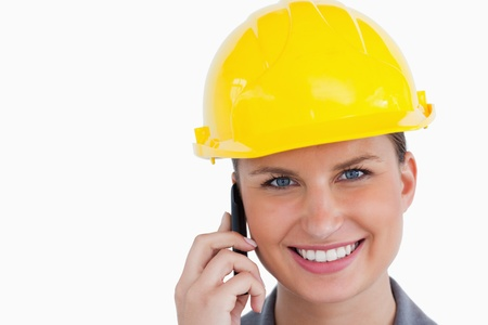 Close up of smiling female architect on her cellphone against a white background photo