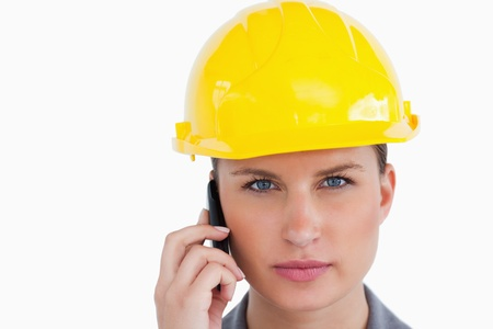 Close up of serious female architect on her cellphone against a white background Stock Photo - 13653163