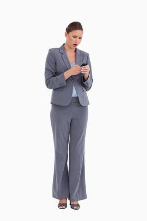 tradeswoman: Shocked tradeswoman reading text message against a white background Stock Photo