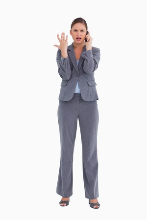 Tradeswoman getting bad news via cellphone against a white background photo