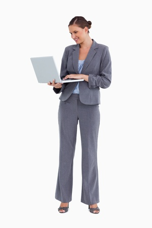 Smiling tradeswoman working on her laptop against a white background photo