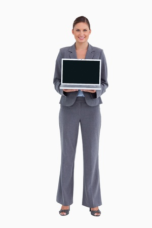 Smiling tradeswoman presenting her laptop screen against a white background photo