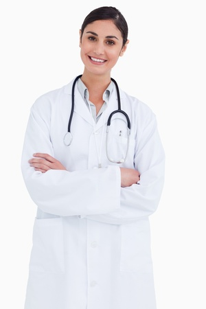 Smiling female doctor with arms folded against a white background photo