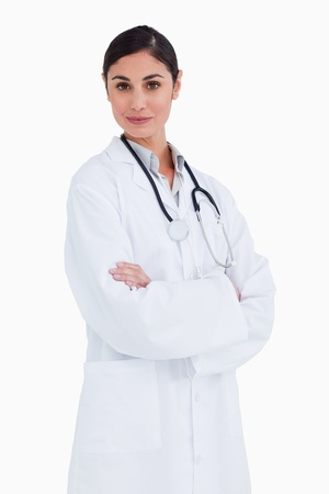Female doctor standing with her arms folded against a white background photo