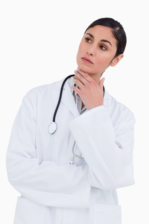 Thoughtful female doctor against a white background photo