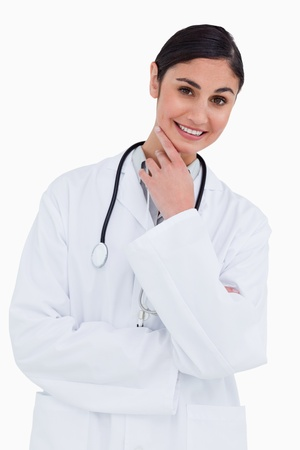 Smiling female doctor in thinkers pose against a white background Stock Photo - 13653261