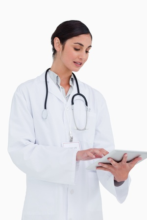 Side view of female doctor with tablet computer against a white background photo