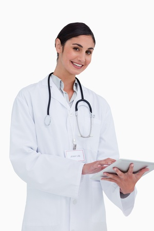 Side view of smiling female doctor with tablet computer against a white background photo