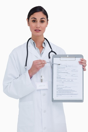 Female doctor pointing at form against a white background photo