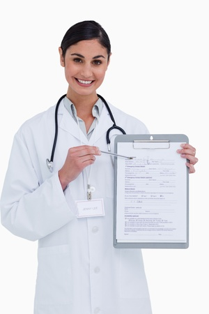Smiling female doctor pointing at form against a white background photo
