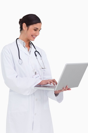 Side view of smiling doctor with her laptop against a white background Stock Photo - 13653052