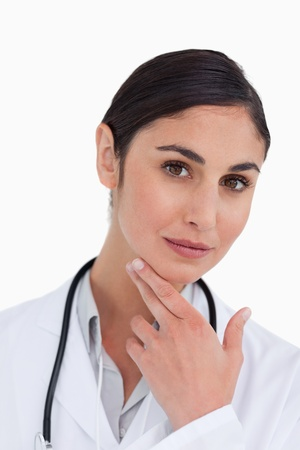 thinkers: Close up of female doctor in thinkers pose against a white background Stock Photo
