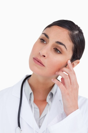 Close up of thoughtful female doctor against a white background Stock Photo - 13653488