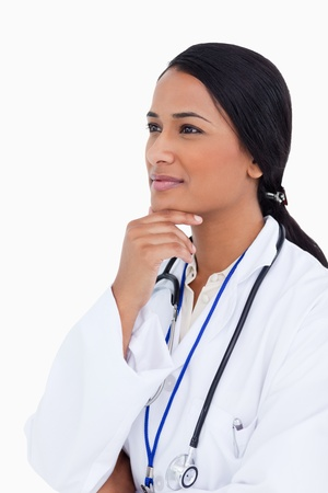 thinkers: Close up of female physician in thinkers pose against a white background