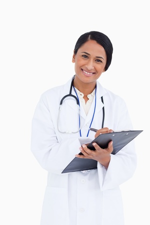 Close up of female physician taking notes on her clipboard against a white background photo
