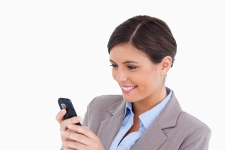 Close up of smiling female entrepreneur reading text message against a white background photo
