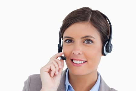 Close up of smiling female call center agent adjusting her headset against a white background photo