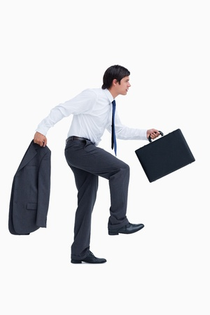 Side view of walking tradesman with suitcase and jacket against a white background photo