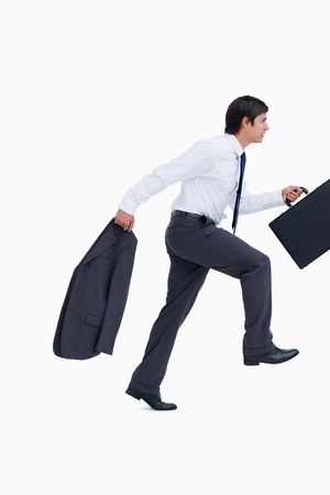 Side view of sprinting businessman with suitcase and jacket against a white background photo
