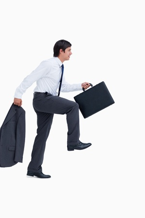 steps to success: Side view of walking tradesman with jacket and suitcase against a white background
