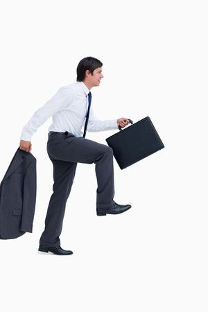 subiendo escaleras: Vista lateral del pie comerciante con la chaqueta y una maleta sobre un fondo blanco Foto de archivo