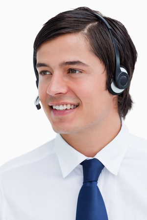 Close up of smiling male call center agent looking to the side against a white background photo