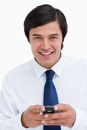 Close up of smiling tradesman holding his cellphone against a white background photo