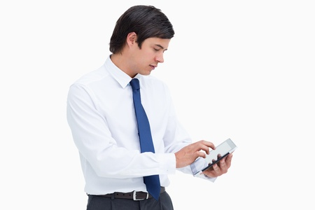 Side view of tradesman using tablet computer against a white background photo