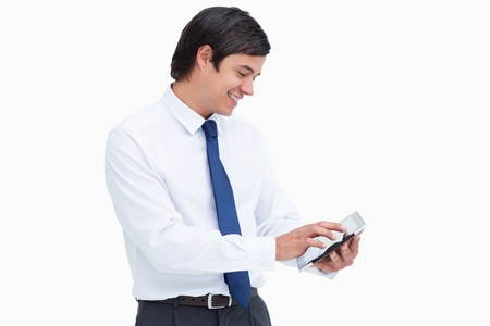 Side view of smiling tradesman using his tablet computer against a white background photo