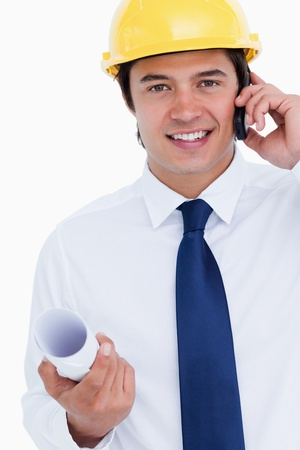 Close up of smiling male architect on his cellphone against a white background photo